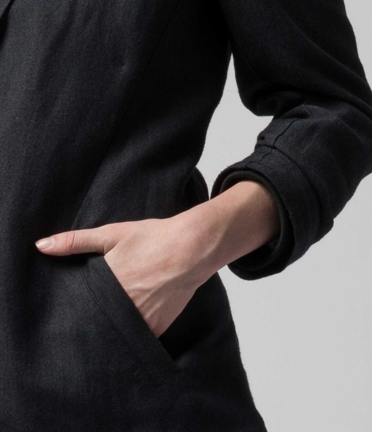 A close up of a woman's hand in her blazer pocket