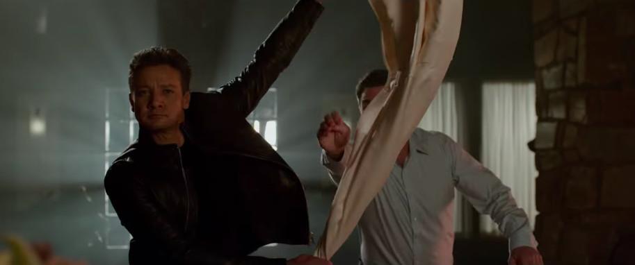 Jeremy Renner draping a blanket over Jon Hamm