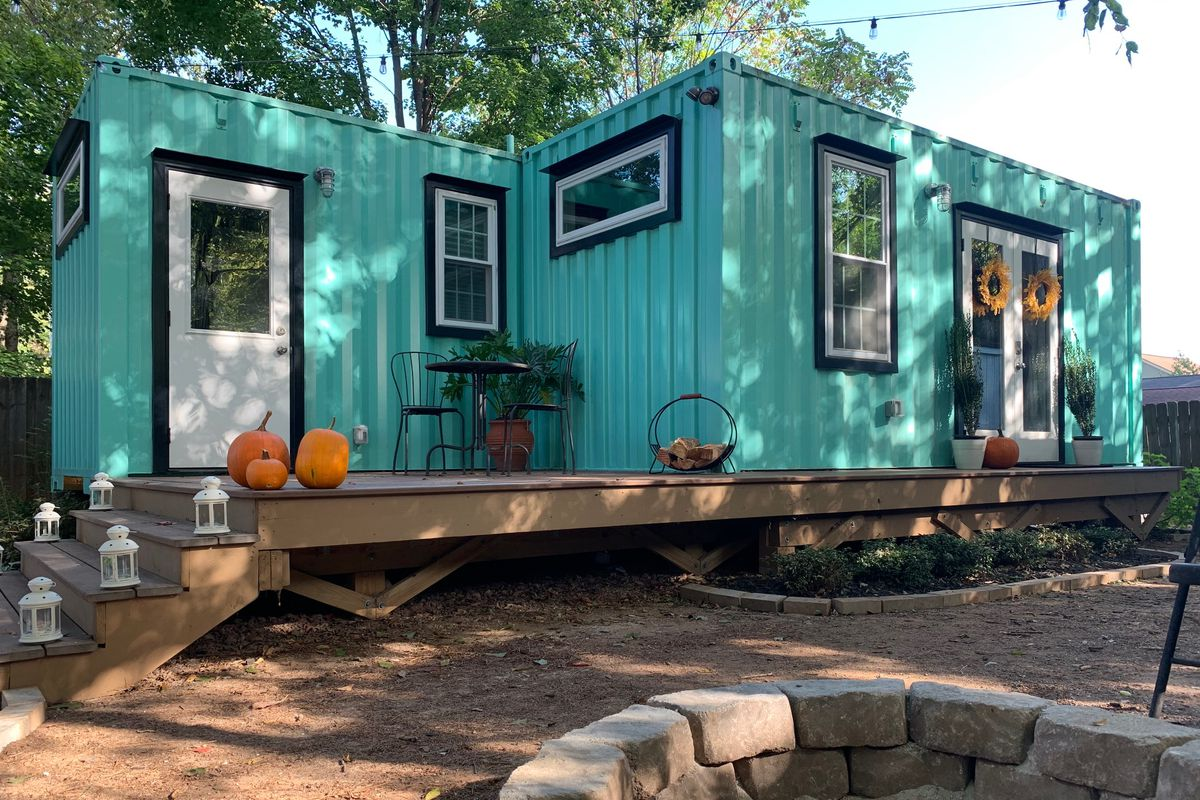 A light blue rental home made of shipping containers.