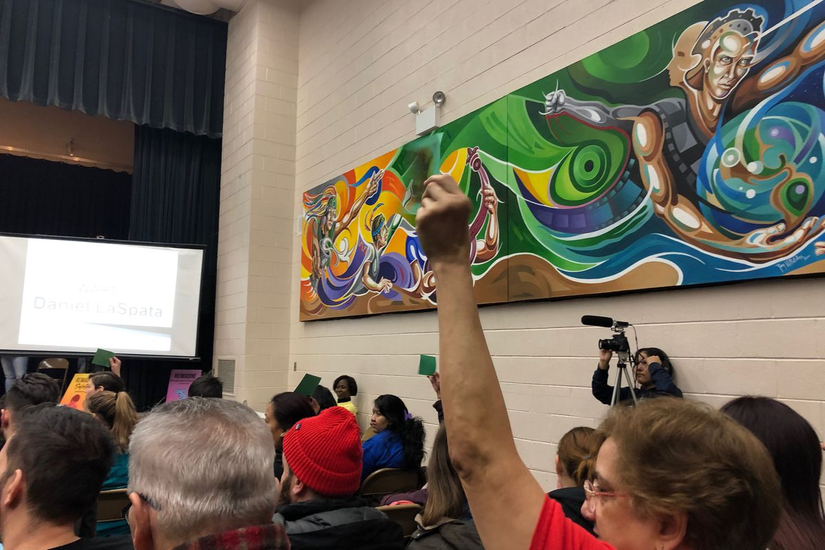An audience member holds up a green sign showing support at a forum for Northwest side aldermanic candidates. The forum was sponsored by the Logan Square Neighborhood Association.