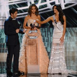 From left, recording artist and host Nick Jonas and television personality and host Giuliana Rancic look on as Miss Utah USA Marissa Powell picks a question to answer during the interview portion of the Miss USA 2013 Pageant Sunday, June 16, 2013, in Las Vegas.