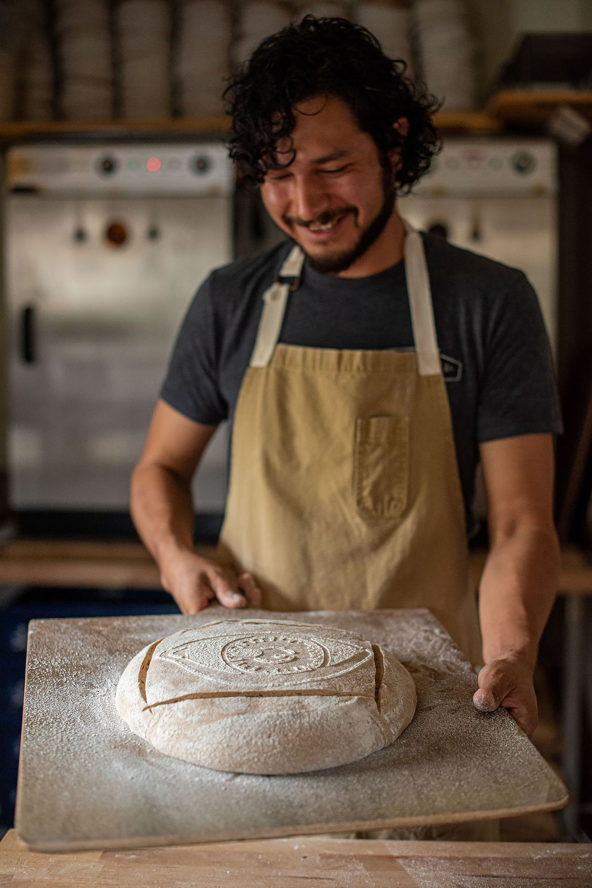 A baker smiles at his raw dough before sending it into the oven.