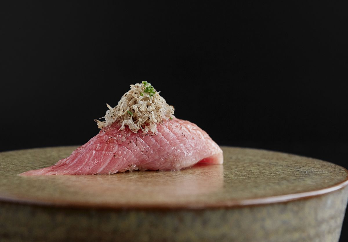 A slice of pink tuna belly with some shavings of ginger on top