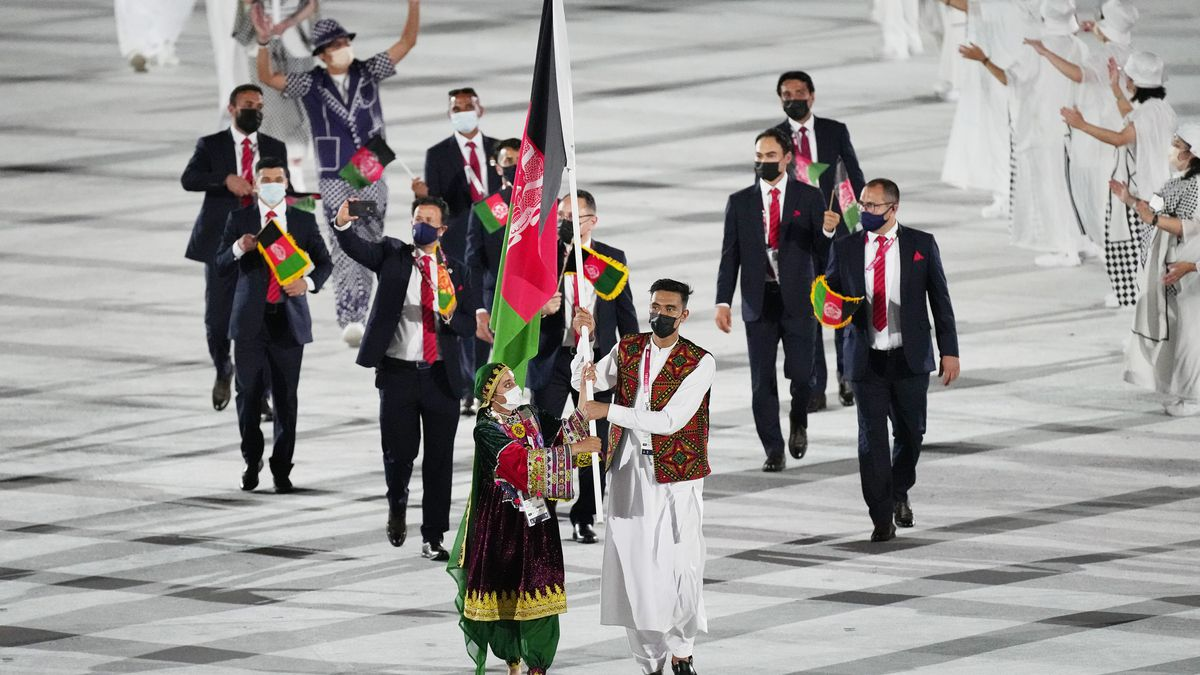 Kimia Yousofi and Farzad Mansouri, of Afghanistan, carry their country's flag at the 2020 Summer Games' opening ceremony.