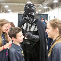 Three young attendees meet a fan dressed as Darth Vader during Salt Lake Comic Con FanXperience.