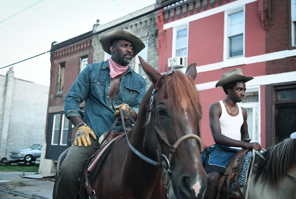 Idris Elba as Harp and Caleb McLaughlin as Cole riding horses in Concrete Cowboy