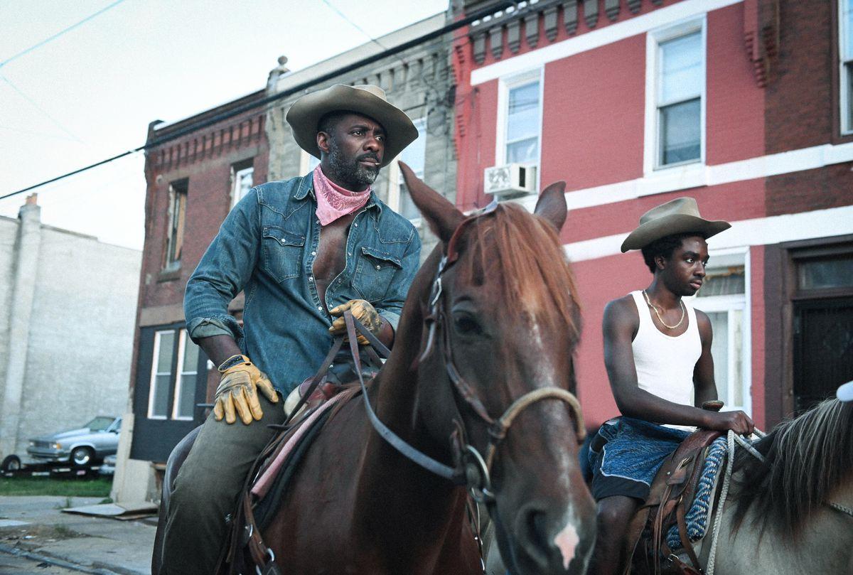 Idris Elba como Harp y Caleb McLaughlin como Cole montando caballos en Concrete Cowboy