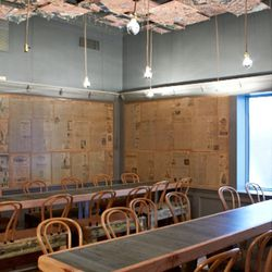 Italian newspapers line the walls around communal tables