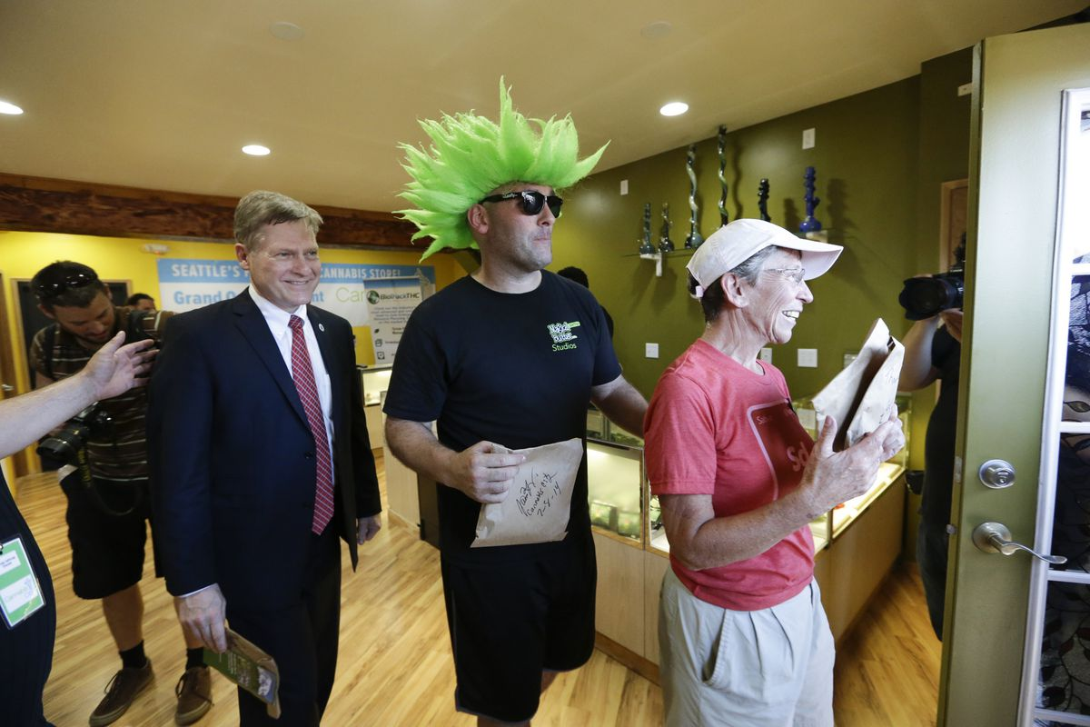 Seattle City Attorney Pete Holmes, Jeremy Cooper, and first customer Deb Greene exit after purchasing marijuana at Seattle's Cannabis City.