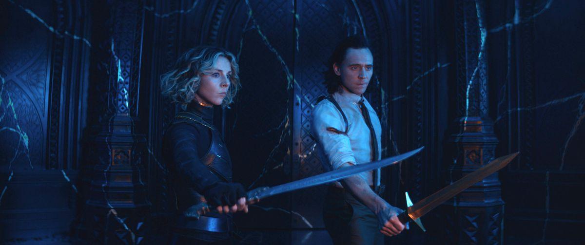 Sylvie (Sophia Di Martino) and Loki (TomHiddleston) in the Citadel holding swords in Loki season 1