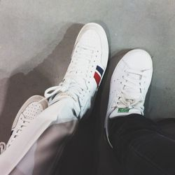 My other seat mate, Leandra Medine, aka the Man Repeller, and I compare sneakers (hers are <b>Saint Laurent</b>). <b>White sneaks are huge this Fashion Week, especially Stan Smiths. Actually, pretty much everyone in Paris is wearing them. Maybe I should s