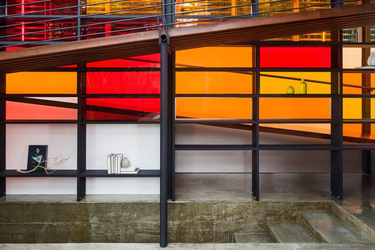 A modernist-looking wall of orange and red glass grid with a ramp in front and bookshelves behind