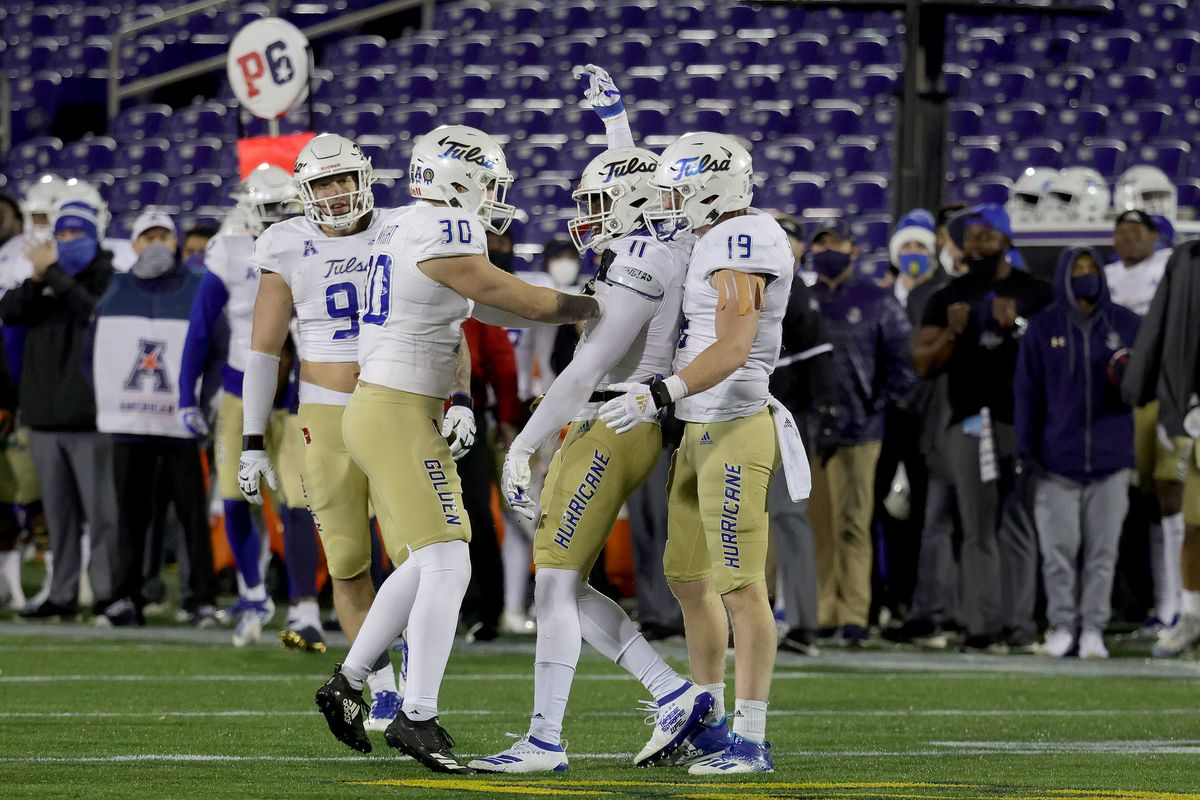 Linebacker Treyvon Reeves of the Tulsa Golden Hurricane celebrates with Justin Wright and Grant Sawyer after making a tackle against the Navy Midshipmen in the fourth quarter at Navy-Marine Corps Memorial Stadium on December 05, 2020 in Annapolis, Maryland.