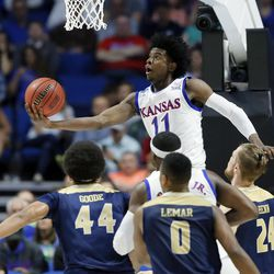 FILE - In this March 17, 2017, file photo, Kansas's Josh Jackson (11) goes up for a shot over UC Davis's Garrison Goode (44), Brynton Lemar (0) and Mikey Henn (24) in the first half of a first-round game in the men's NCAA college basketball tournament in Tulsa, Okla. Jackson spent one season at Kansas and is expected to be a top-five pick in Thursday's NBA draft.