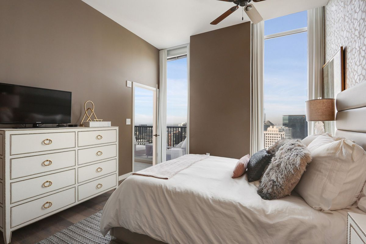 A brown and white master bedroom with views of a city.