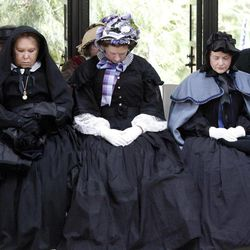 Women in period dress pray during the  military funeral for Civil War veteran Peter Knapp at Willamette National Cemetery in Portland, Ore., Friday, April 13, 2012.  Knapp is the first Civil War veteran buried at Willamette National Cemetery, Oregon's largest veterans' cemetery. His ashes had been sitting on a shelf at the Portland Crematorium since 1924.