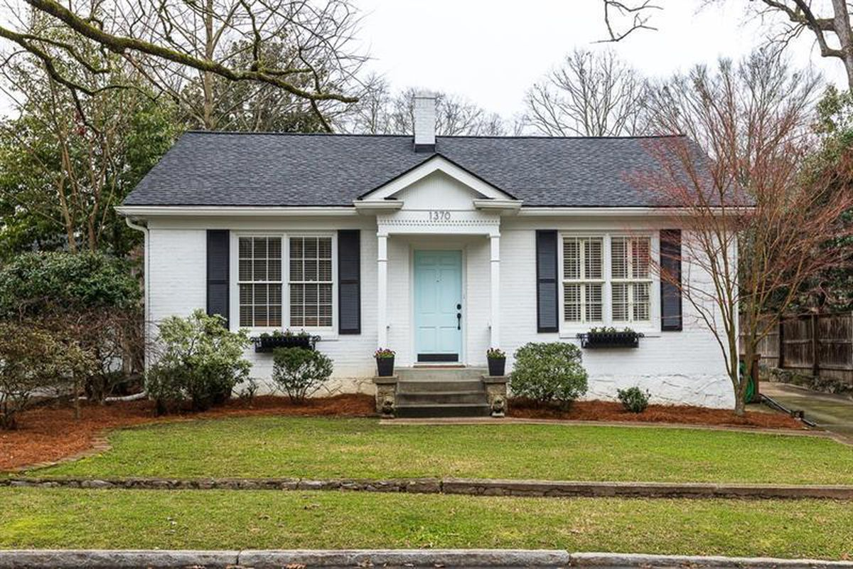 A small white home with a light-blue door and black shutters, with a green lawn in front.
