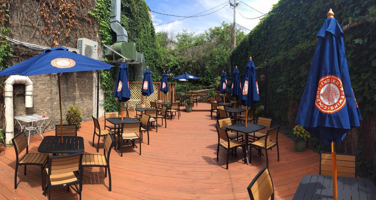 A long, narrow patio with black metal tables and blue umbrellas facing a green, ivy covered wall