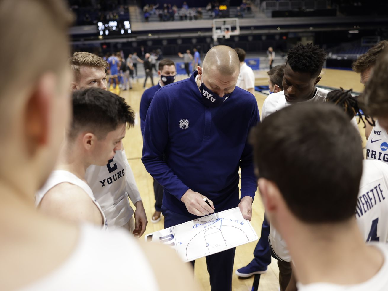 BYU players surround coach Mark Pope during a timeout.