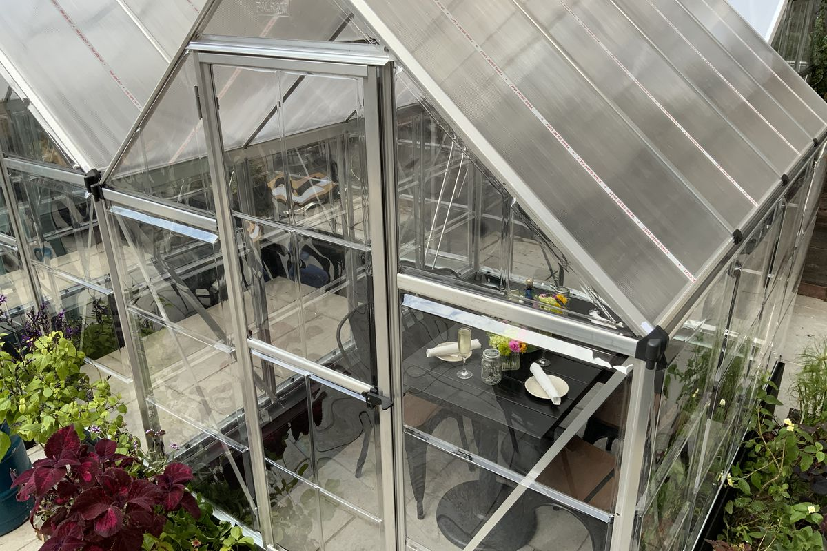 greenhouse with plants outside and a dining table and chairs inside