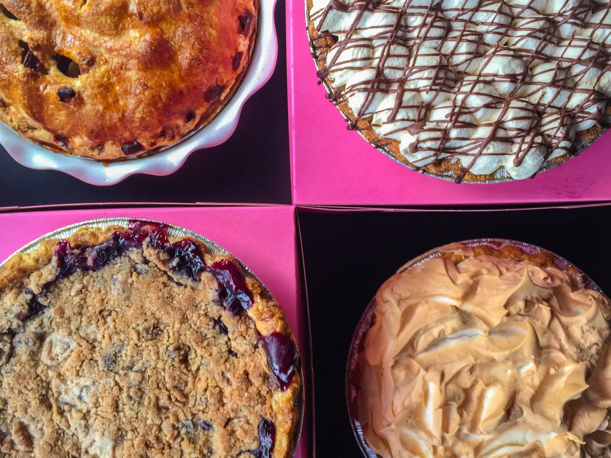 An overhead view of four different pies on a black-and-pink grid