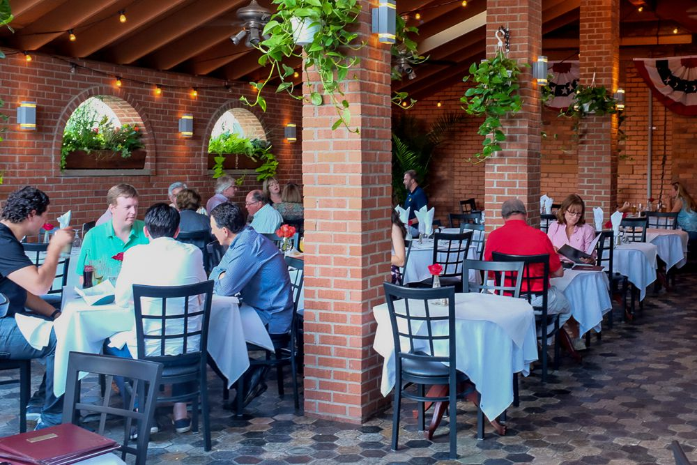 People sit outside at patio tables with white tablecloths surrounded by brick and plants.