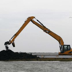 A backhoe is used to release water from a flooded area  in the aftermath of Isaac Friday, Aug. 31, 2012, in Ironton, La. Isaac is now a tropical depression, with the center on track to cross Arkansas on Friday and southern Missouri on Friday night, spreading rain through the regions.