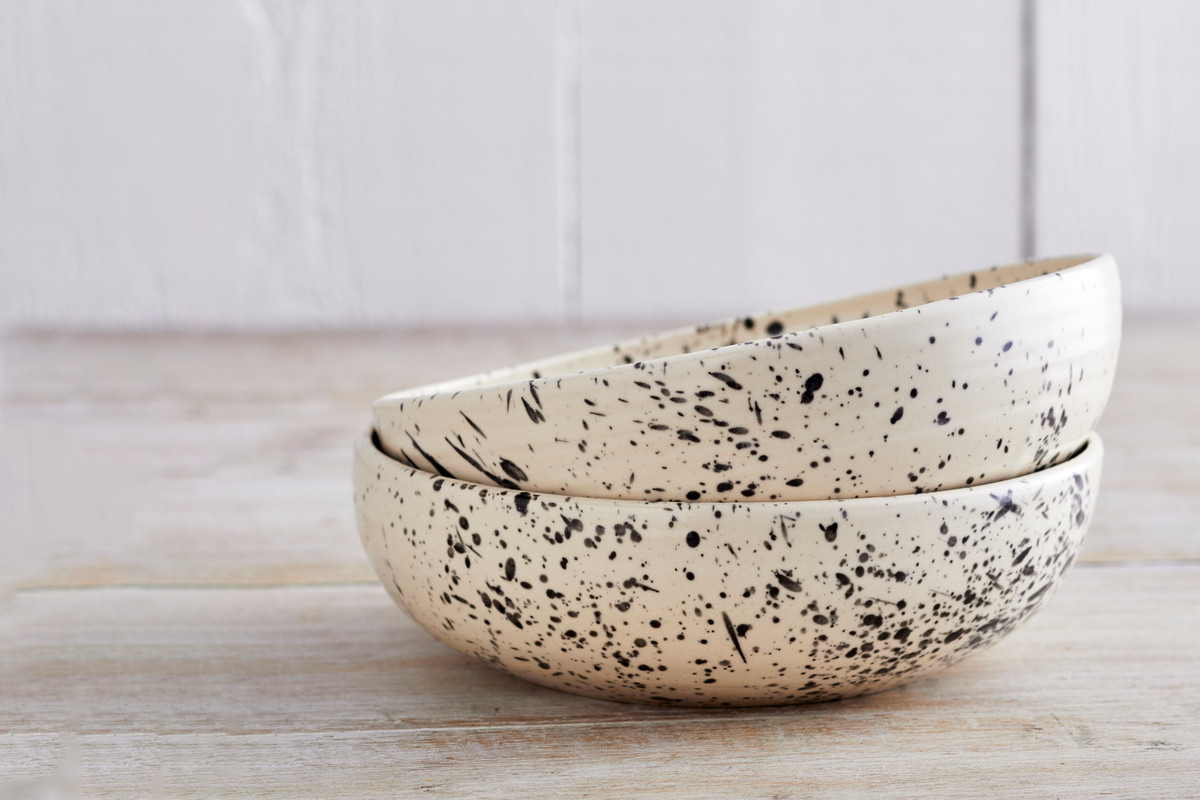 Two stacked bowls sitting on a wooden surface. The bowls both have a black and white splatter pattern.