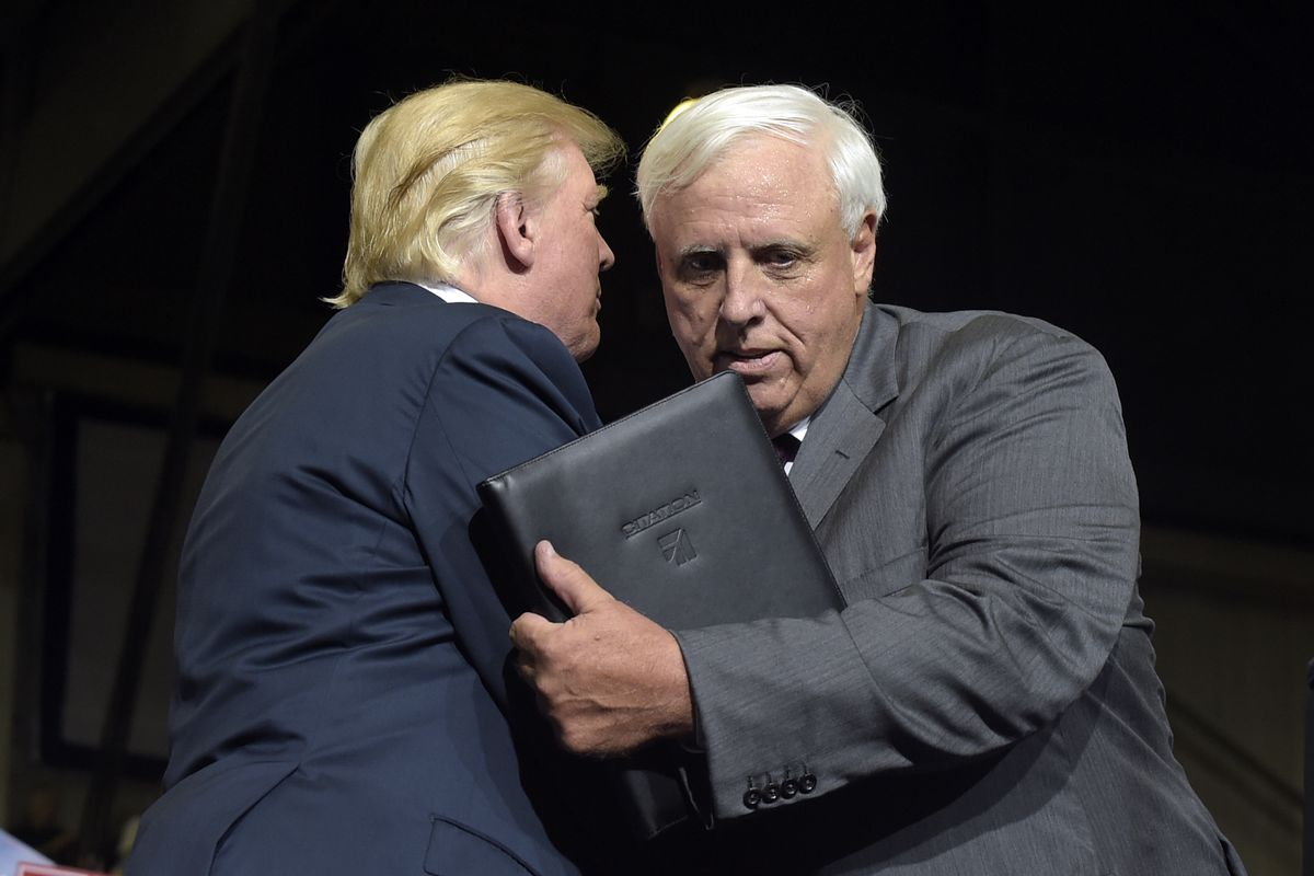 President Donald Trump, left, hugs West Virginia Gov. Jim Justice, right, after Justice announced at a campaign-style rally at Big Sandy Superstore Arena in Huntington, W.Va., Thursday, Aug. 3, 2017, that he is changing parties.