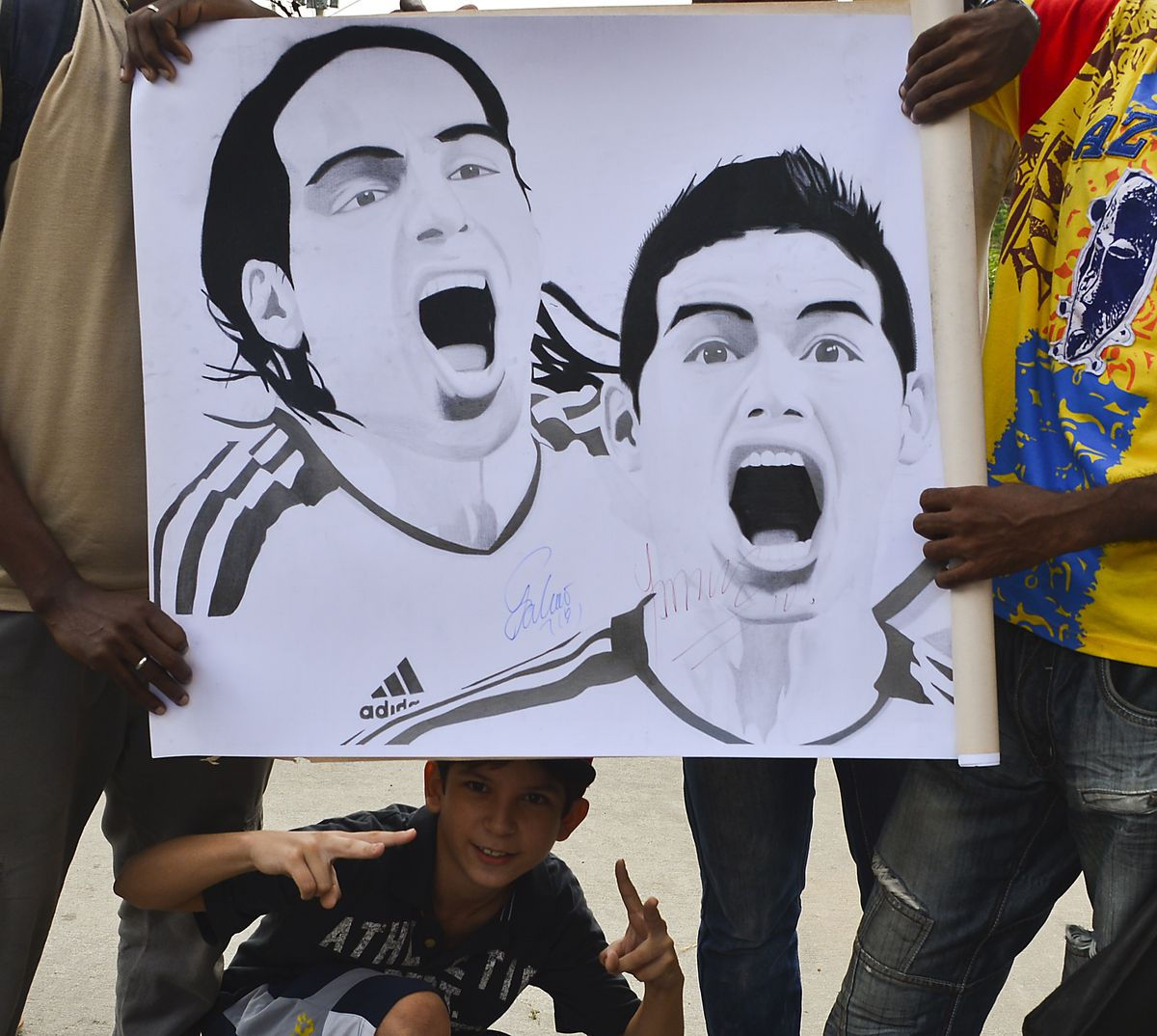 Colombia's national football team fans show a drawing of players Radamel Falcao (L) and James Rodriguez before a training session in Barranquilla, Colombia, on October 9, 2013. Colombia will face Chile in a FIFA World Cup Brazil 2014 qualifier match on September 11.