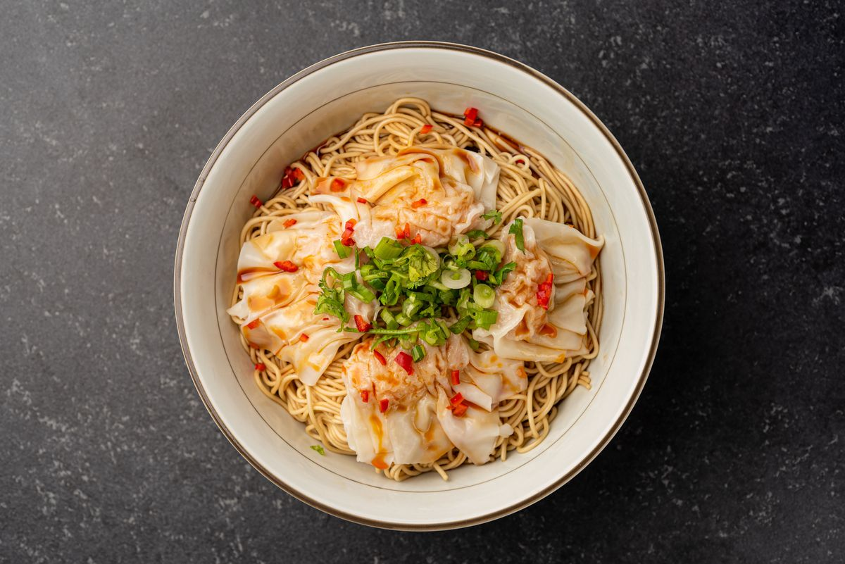 An overhead shot of wontons and noodles in a bowl of soup.