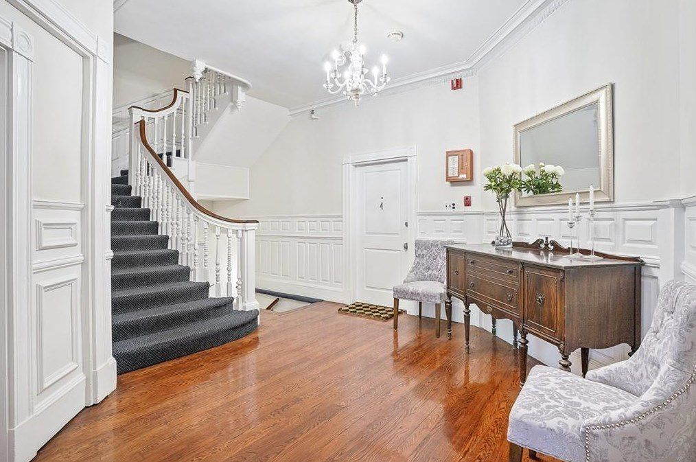 A large stairwell landing with two chairs and a large chest.