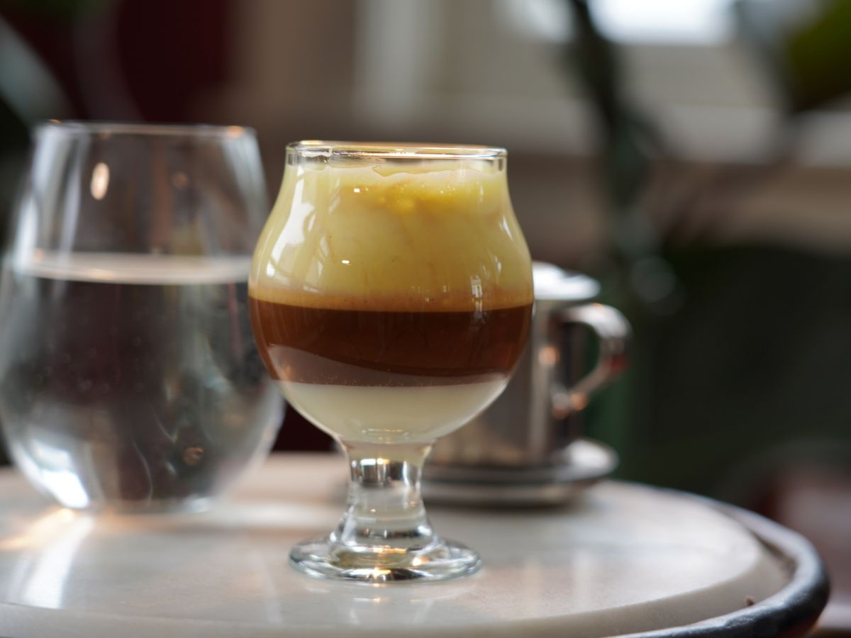 A three-layered coffee drink sits in a curved glass on a white table. There's a milk layer, a coffee layer, and a foam layer visible.