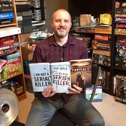 """Professional writer Dan Wells holds up the English and German versions of his novel, """"I Am Not A Serial Killer,"""" along with a book from his top-selling Partials series."""