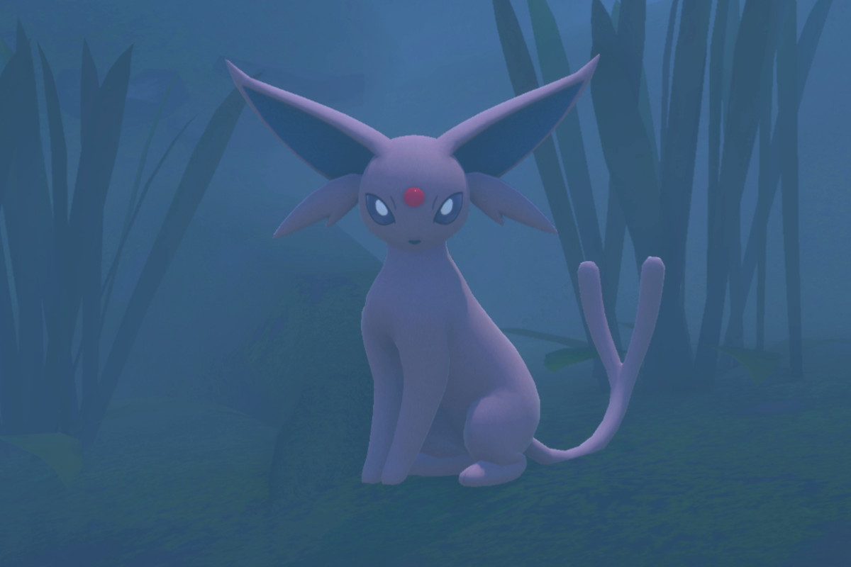An Espeon sits in a foggy forest