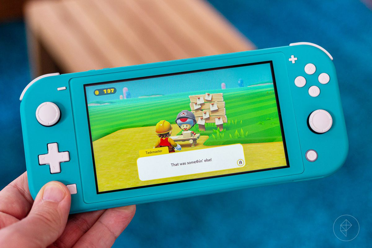 a hand holding up a turquoise Nintendo Switch Lite showing Super Mario Maker 2