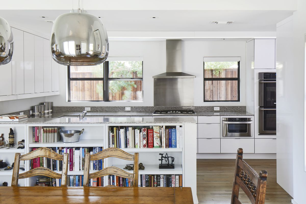 In the foreground is a wooden table with chairs. In the background is a white kitchen with granite countertops. A bookcase built into the kitchen counter divides the space.