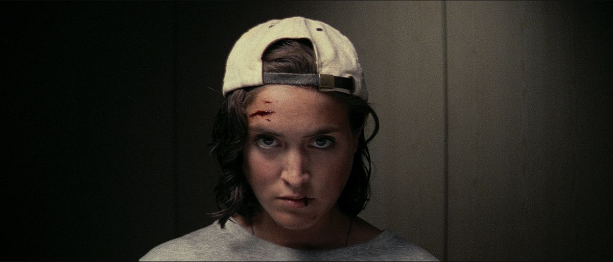 a woman looks defiantly at the camera, blood smeared on her forehead