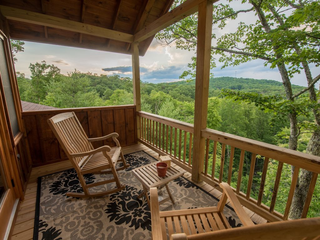 Covered porch with chairs and small table overlooking the mountains.