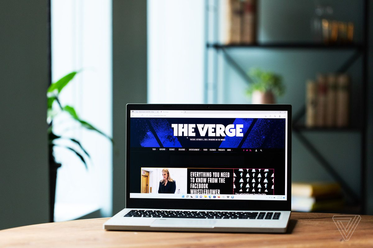 The Acer Aspire Vero open on a wooden table with a bookshelf in the background. The screen displays The Verge homepage.