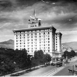The Hotel Utah juts against the sky in an undated early photo. Near the hotel are auto, trolley and horse and buggy.
