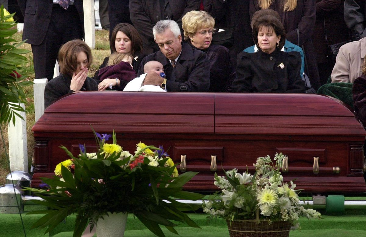 """Shannon Spann (L), widow of slain CIA officer Johnny """"Mike"""" Spann, touches her lips to her hand before touching the casket at the conclusion of Spann's funeral at Arlington National Cemetery on December 10, 2001. Spann's father, Johnny (C), holding his gr"""