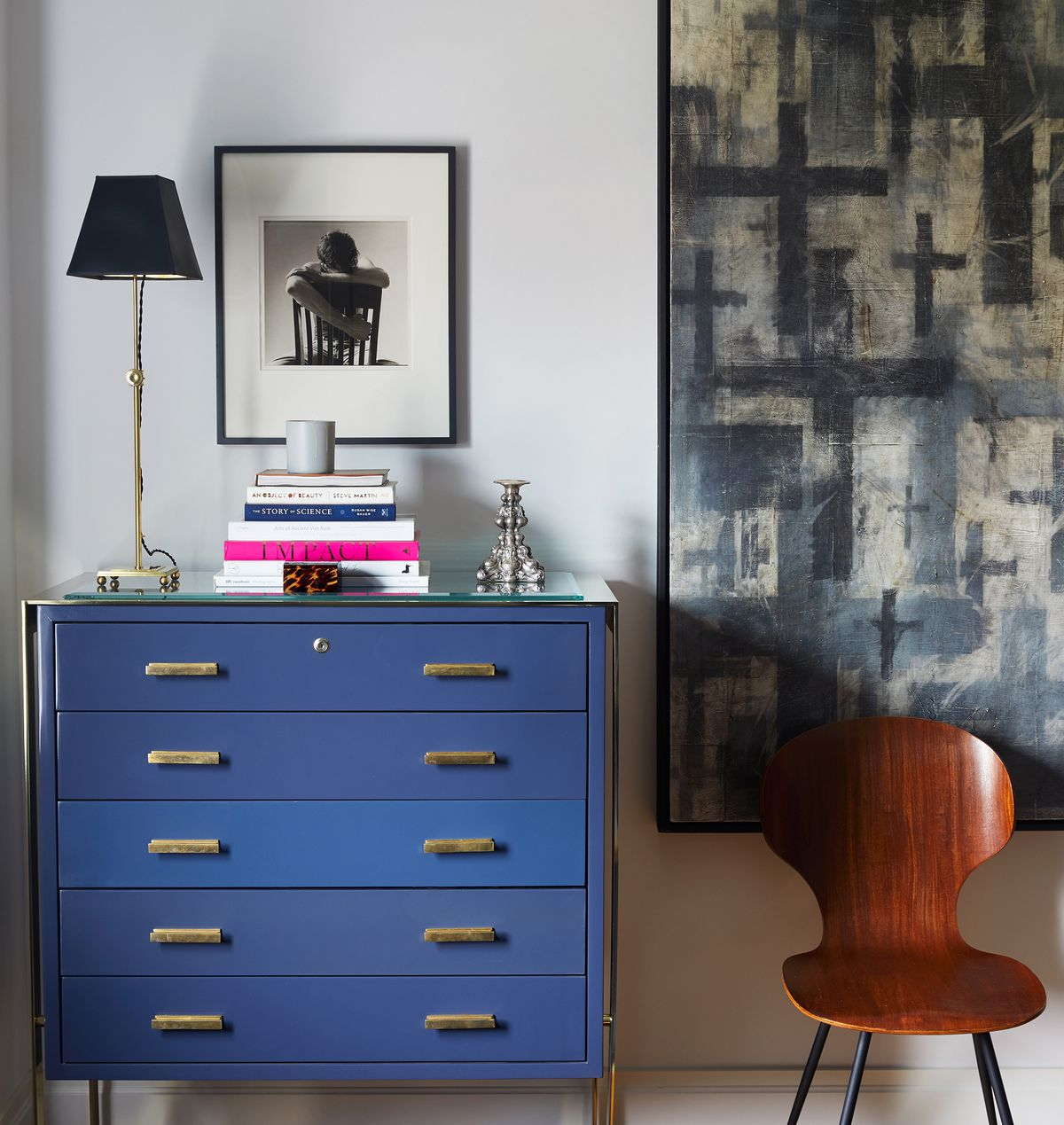 A black and white photo hangs above a blue chest of drawers in the master bedroom.