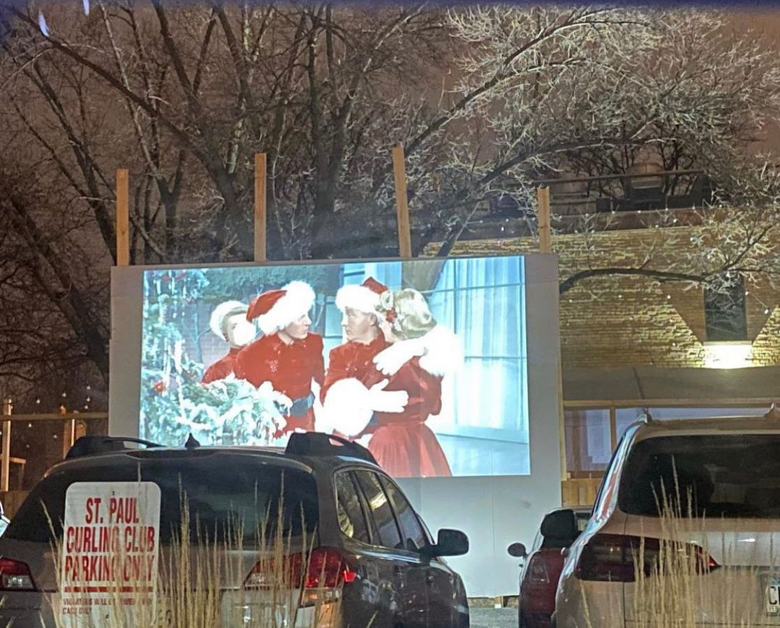 A screen shows Bing Crosby and Danny Kaye dressed as Santas, as viewed from cars parked in The Gnome's parking lot.