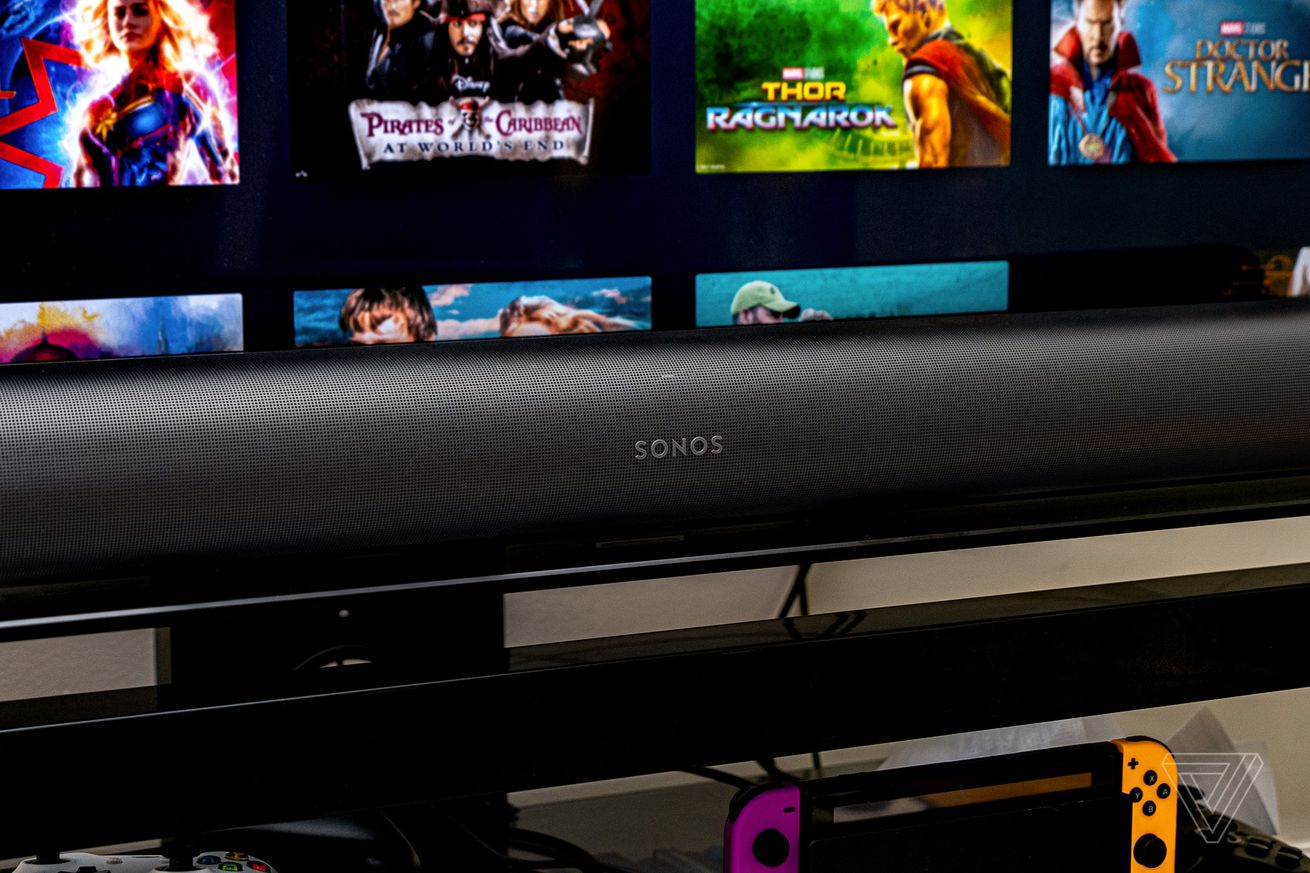 An image of the front of the Sonos Arc soundbar with a TV in the background.