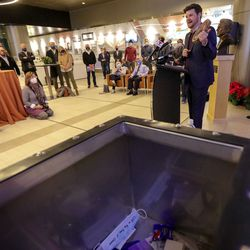 Chris Wharton, Salt Lake City Council chairman, talks about putting a piece of a fallen tree from this year's windstorm into the time capsule, foreground, during a ceremony to mark the 100-year anniversary of the Salt Lake City International Airport in Salt Lake City on Monday, Dec. 21, 2020.