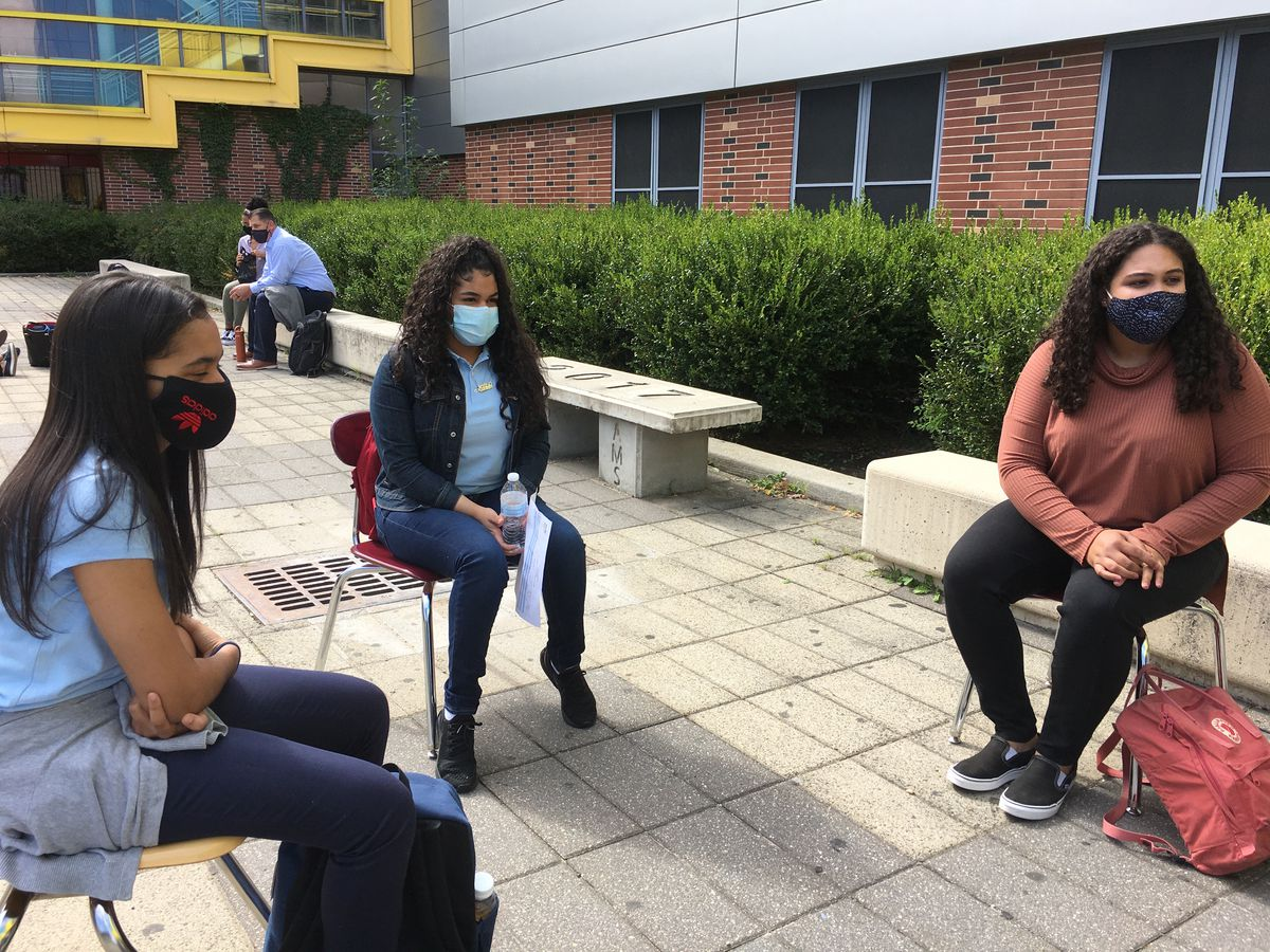 Ashanty Peralta and two friends, each wearing face masks, sitting outside in the school courtyard.