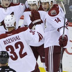 Phoenix Coyotes' Lauri Korpikoski, left, of Finland, Boyd Gordon, center, and Michal Rozsival (32) gather to celebrate a goal by Taylor Pyatt, right, against Minnesota Wild goalie Niklas Backstrom in the first  period of an NHL hockey game on Saturday, April 7, 2012, in St. Paul, Minn.