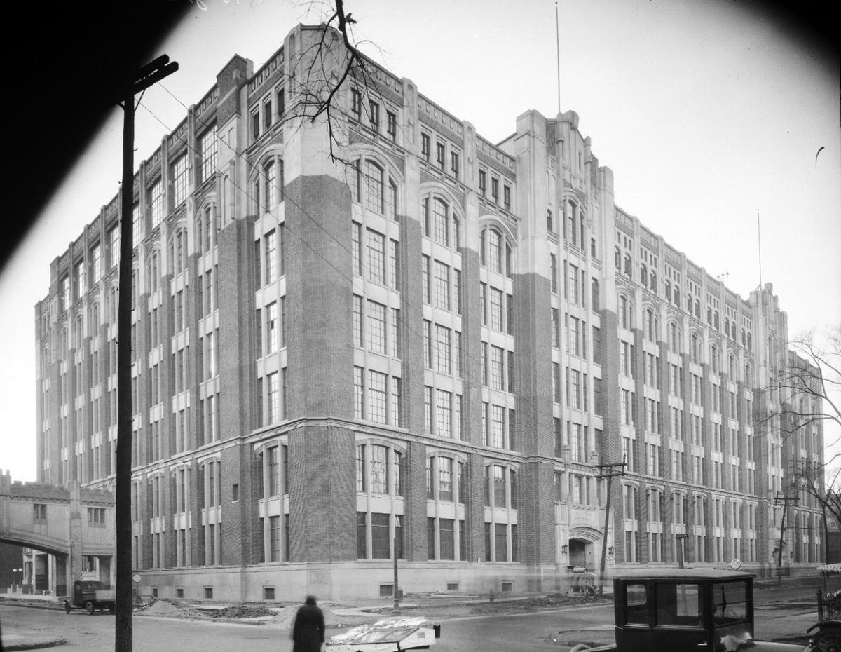 A black and white photograph of a long, rectangular six-story building. Most of it is made of bricks and repeating windows, with the top made of stone.