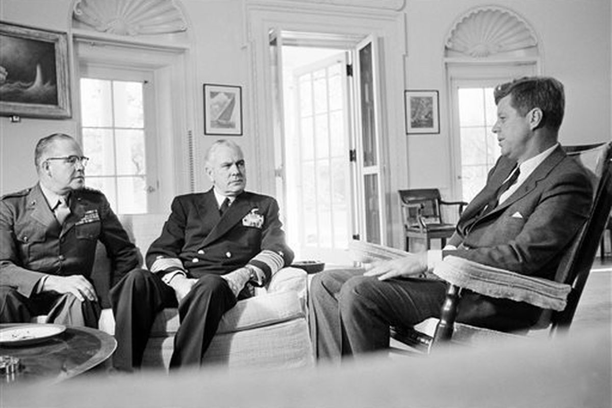 In this Oct. 29, 1962, file photo, President John F. Kennedy poses in the White House office with Gen. David Shoup, left, Marine Corps Commandant, and Adm. George Anderson, Chief of U.S. Naval Operations in Washington. The chiefs met with the president to